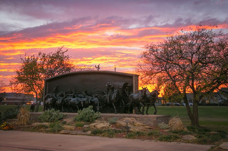Sunset on the Chisholm Trail serves as a grand backdrop for the On the Chisholm Trail monument, Thursday, Nov. 17, 2016. Duncan, OK - Chisholm Trail Heritage Center.