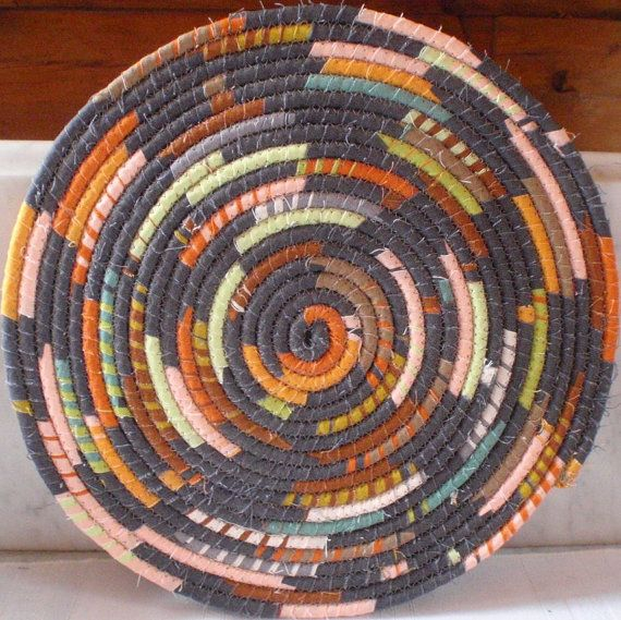 This mat is 12 in diameter and is made from strips of a contemporary print fabric that are wrapped around cording, coiled and sewn with a zigzag stitch. It has medium tone colors of pumpkin orange, peach, lime green, brown, teal and tan against a charcoal gray background. Use it as a hot pad or trivet, a placemat or as an interesting table mat to keep vases, figurines, lamps and such off the table. It also makes a great one of a kind gift!  The listing is only for the mat. The bowl and other…