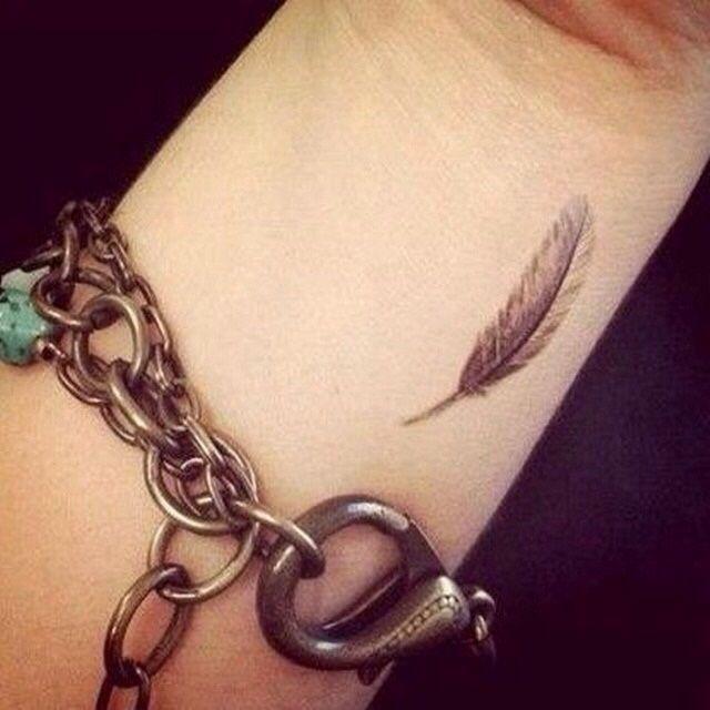 Piccola piuma tatuata sul polso