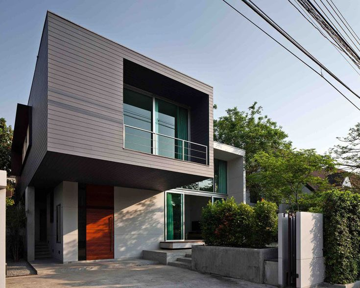 Lynk Architect have designed this two-storey house with a cantilevered bedroom in the outskirts of Bangkok, Thailand.
