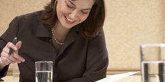 Une jeune femme est assise à un bureau et regarde un document. Elle travaille sur ce dossier crayon à la main. Programme Administration des affaires – gestion de La Cité collégiale.