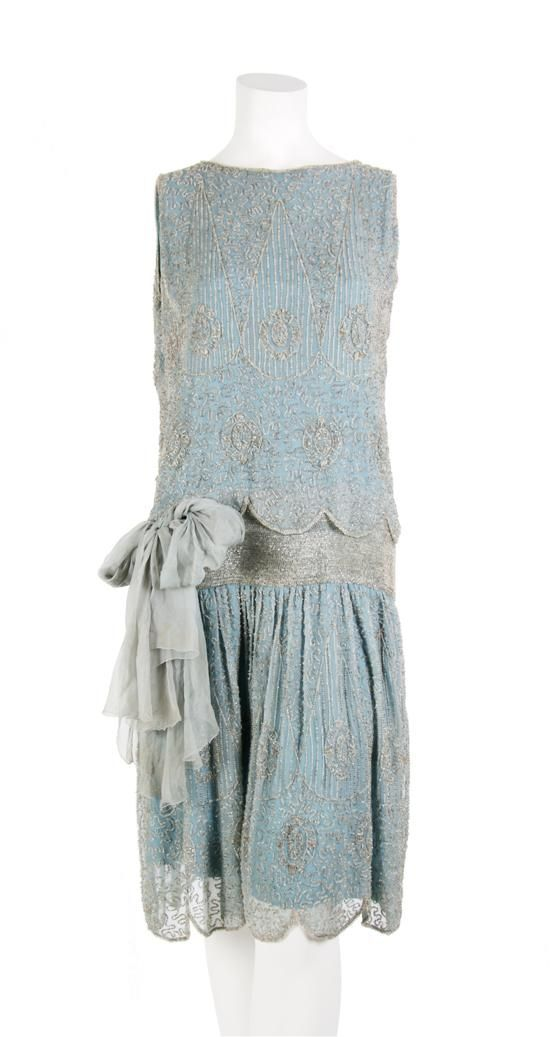 Cocktail dress ca. 1920s. Blue silk chiffon, beaded all over. Sash at dropped waist; fully lined.