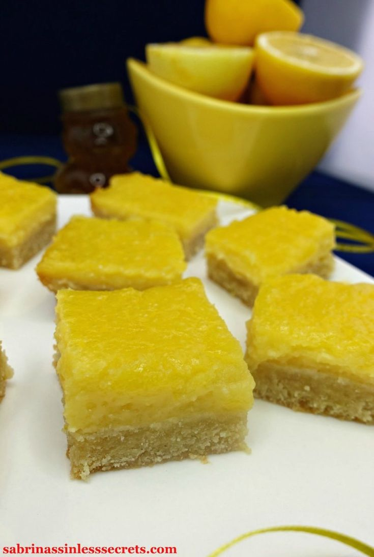 Homemade Paleo Lemon Bars with a Shortbread Crust scattered on a white, square plate with a sparkly, white cloth napkin on the side of it, along with yellow with white dotted ribbon, a honey bear, and a yellow bowl or half-sliced lemons