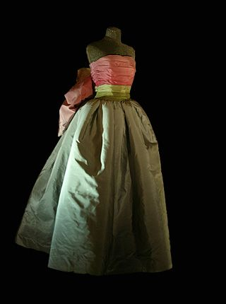 1995 - Worn by Queen Silvia of Sweden to Nobel Banquet. A Nina Ricci creation This gown has a wide tafetta skirt in tones of light  and dark grey, topped by a pink bodice with a green belt that ends in rosette-like flowers at the back.