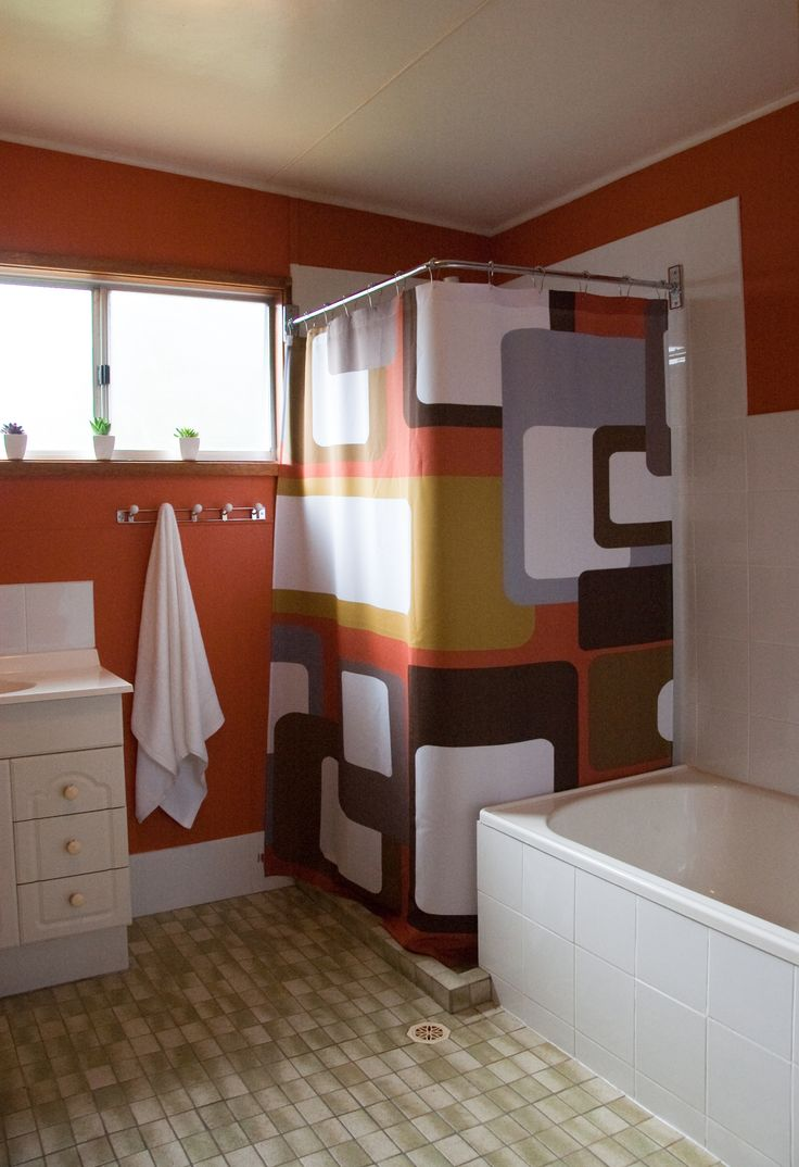 The bathroom was large but only had a bath and a tiny vanity. We added  double vanity and a separate shower - complete with funky curtain. The walls were painted to match. TIP: Undercoat with grey when painting with orange or it just won't cover properly.