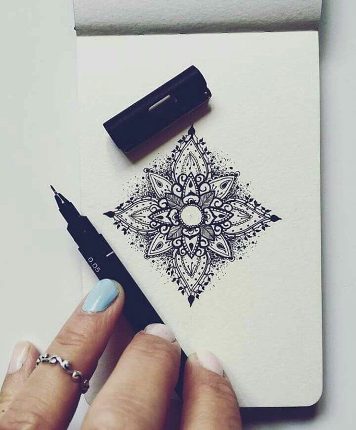 small notebook, small mandalas in square shape, black pencil, woman hand, painted nails