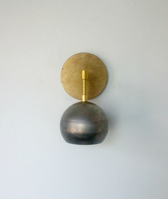 The Loa Sconce in steel and brass is composed of one standard-sized socket with a steel globe shade. The contrast between the steel and brass is