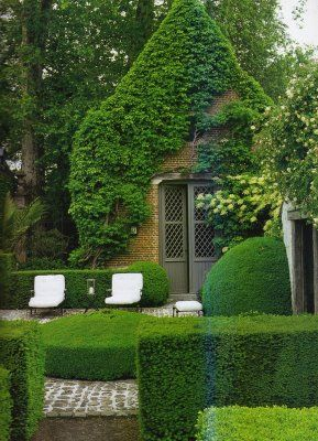 Clipped yew hedging encloses a garden with topiary -  'disc' of box surrounded by attractive paving stones as well as the chunky yew topiary leaning against the wall.