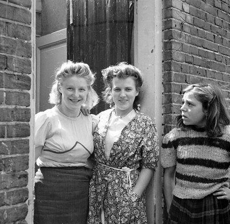 """Twee jonge vrouwen en een meisje in de deuropening van een huis, waarschijnlijk in de Oranjestraat te Utrecht.Eind jaren 40, begin jaren 50. De foto werd gemaakt in opdracht van de Zusters Augustinessen voor mogelijke plaatsing in hun maandblad """"De Stad Gods"""