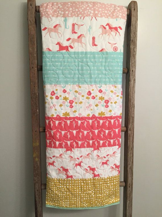 This adorable cowgirl themed whole cloth baby quilt features horses, Longhorns, cowgirl hats and boots, and horse shoes in pink, coral, mint, light aqua and gold. It would be a perfect gift for that special little cowgirl or horse lover in your life!! It is a generously sized quilt constructed of three layers with natural cotton batting in the middle, and quilted in a meandering loopy pattern to keep layers from shifting. Would also be great for a car seat or stroller quilt or for tummy time…