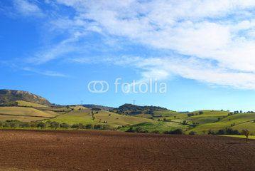 Paesaggio con terreno arato in primo piano, delle colline sullo sfondo e le nuvole nel cielo azzurro #microstock #marketing #webdesign #design #WebContent #SEO #csstemplates #css #HTML5 #Websites #web20k #web2015 #web