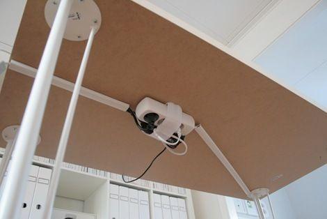 BUENÍSIMO! Esconder los cables usando canaletas y sujetando con velcro los accesorios eléctricos. Los cables son blancos se fijaron a la pata del escritorio con cintillos plásticos y en el piso se usó una canaleta del mismo color.