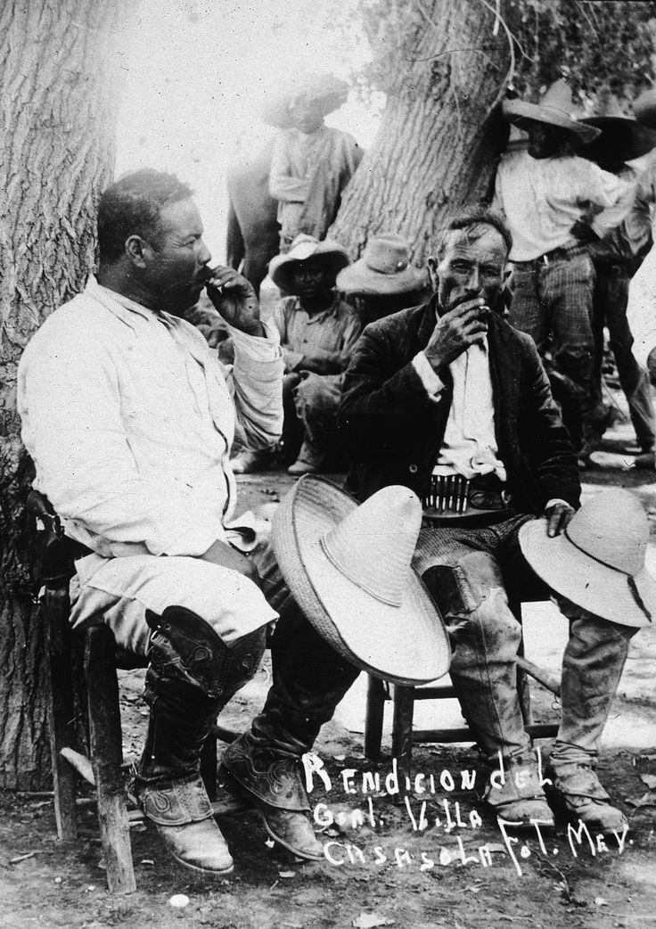 Mexican revolutionary leader Pancho Villa (1878 - 1923), left, sits against a tree with a fellow soldier following the Mexican Revolution of 1911. Many of Pancho Villa's soldiers were indigenous Yaqui Indians and they were very fond of smoking 'motas' – marijuana cigarettes. (Photo by Hulton Archive/Getty Images)