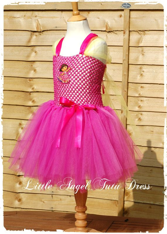 Dora the Explorer Dress - Handmade Tutu Fancy Dress Costume  This beautifully cute Dora the Explorer dress has been handmade using a hot pink tutu top and hot pink and dark yellow layers and layers of tulle. I have then attached a Dora motif at the front of the top. To finish of the cute look, I have added a hot pink bow using a ribbon. As many of us know Dora the Explorer is a much loved childrens TV series which is addored by many children around the world. My Inspiration was taken from…