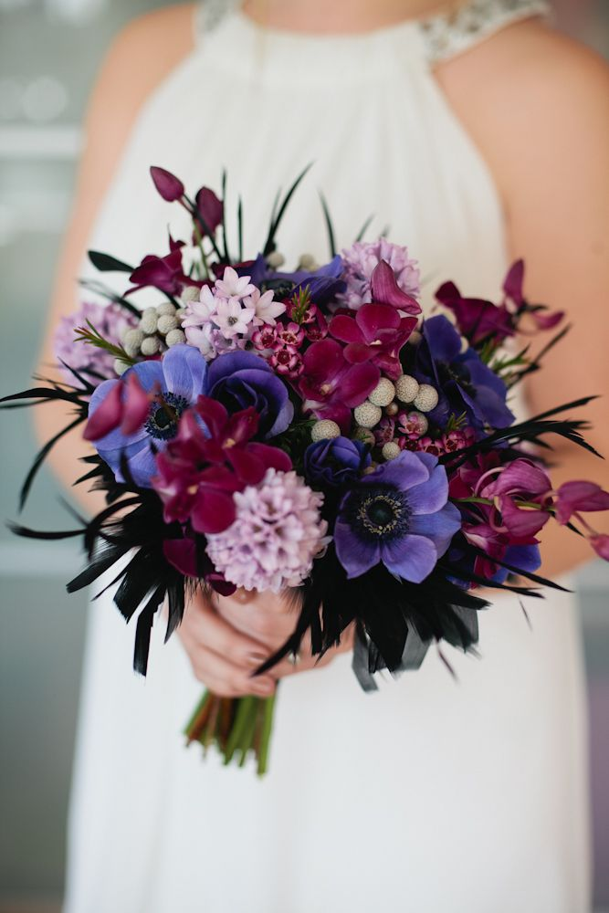 purple dendrobium orchids, lavender hyacinths, blue anemones, gray berzelia berries, black feather plumes, and a touch of purple wax flower.