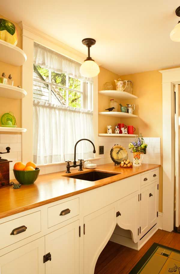 "love the flipper doors! In the pantry, wood countertops surround a copper sink. A dishwasher is hidden behind false drawer fronts. The ""flipper doors"" under the sink add a period touch."