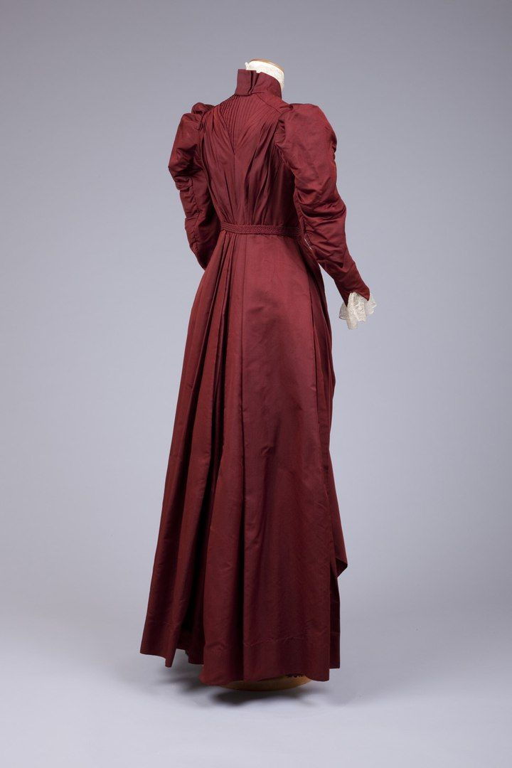 Шёлковое платье, 1889-1892. Brick Red Silk Dress One-Piece Rather Short Waistline With Braided Belt Tied In Front With Tasseled End. Skirt Has Elaborately Draped Front and Center Back With Many Deep Folded Pleats, But Not A Bustle. Sleeves Are Long and Fuller At The Shoulder, But Not Really Leg-O-Mutton Sleeves. Transition Dress From 1880S To 1890S. Goldstein Museum of Design.