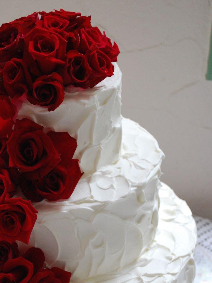 バラと繊細で柔らかな印象をあたえるペタペタしたクリーム使いが素敵なウエディングケーキ。真っ赤なバラがロマンティック。