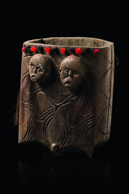 India, Naga  wood, brown patina, the front side carved with two anthropomorphic heads and curvilinear ornaments, a row of drilled holes on the upper rim with tufts of red and black dyed goats hair inserted, back board made of wickerwork, plant fibre eyelets for suspension, human hair, slightly dam., crack (bottom/backside)  Read more: http://www.tribal-art-auktion.de/en/catalogue184/d50_1/#ixzz3z7Ff9ImN