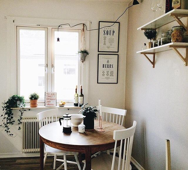 Sweet and simple breakfast nook. Round table, white chairs, mounted shelves, old radiator, and plants for extra beauty.
