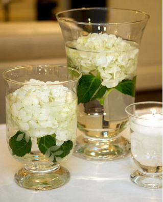 Hydrangeas submerged in hurricane vases - could be used on guest tables