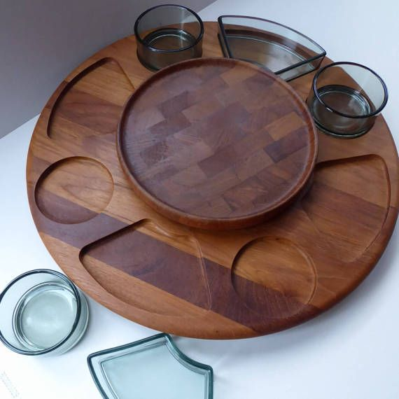 This is a fabulous vintage 1960s Scandinavian Lazy Susan. It is a very good quality example made by the celebrated company Digsmed.  The company designed and produced high quality household goods. They were best known for their fine Lazy Susans and rotating spice racks. The Lazy Susan has a concealed rotating wooden circle under the base - and on the top has little indentations for holding glass dishes in place as the serving platter revolves. Digsmed collaborated with the Danish glassworks…