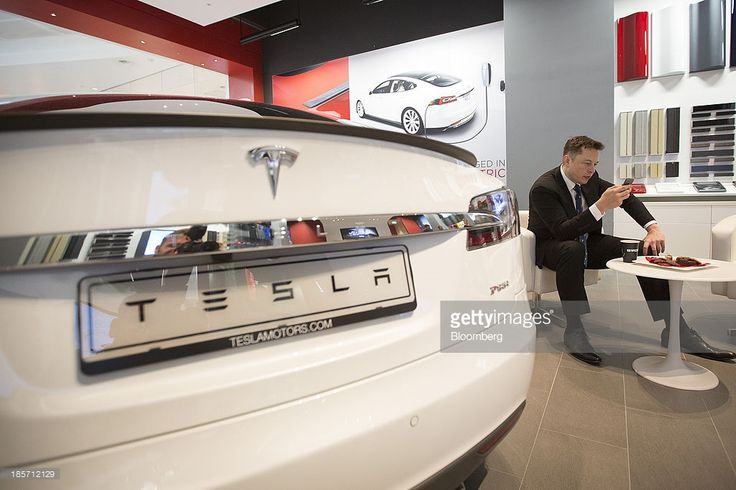 Elon Musk, billionaire, co-founder and chief executive officer of Tesla Motors Inc., checks a mobile device as a Tesla Model S automobile sits on display in the Tesla store at Westfield Stratford City retail complex in London, U.K., on Thursday, Oct. 24, 2013. Tesla, the electric-car maker led by Musk, had its first quarterly profits this year with a boost from selling California pollution credits. Photographer: Simon Dawson/Bloomberg via Getty Images