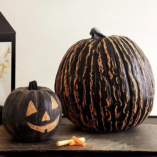 """These chalkboard paint pumpkins are the perfect way to say, """"Happy Halloween!"""" Simply paint, then use chalk to add a message, face, or eerie pumpkin pattern."""
