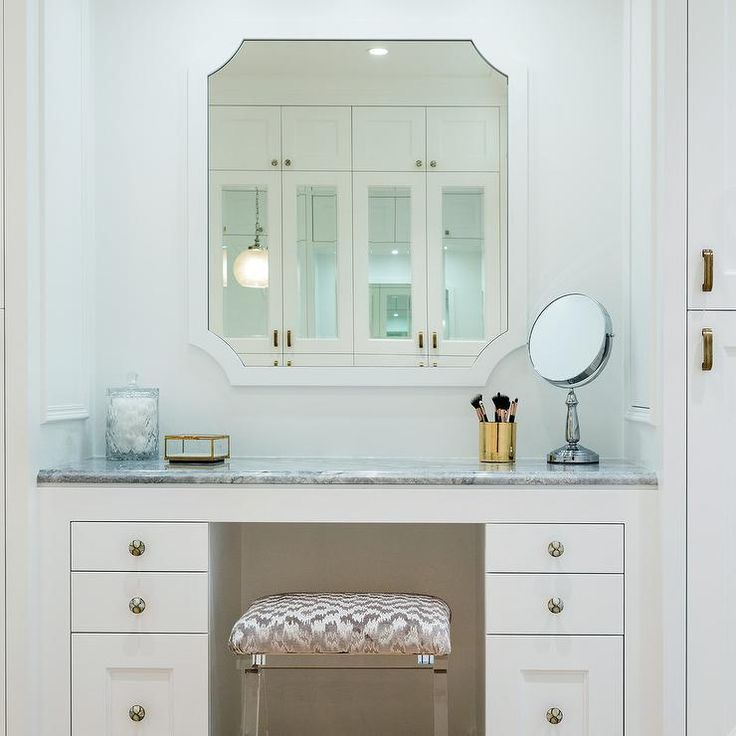 A gray chevron stool sits at a white dressing table accented with mirrored knobs and a gray marble countertop fixed beneath a white framed mirror with clipped corners.