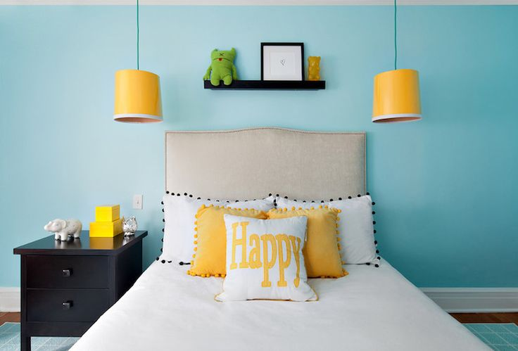Adorable girl's room with yellow hanging lamps either side of headboard on walls painted Benjamin Moore Blue Seafoam over hardwood floors layered with an aqua blue grid patterned rug. The bedroom features a small black display ledge over the linen studded headboard accented with white bed linens topped with black pom pom trimmed pillows, yellow pom pom trimmed pillows and a yellow happy pillow flanked by a black nightstand.