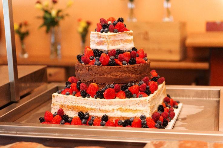 Třípatrový naked cake svatební dort dozdobený čerstvým ovocem.