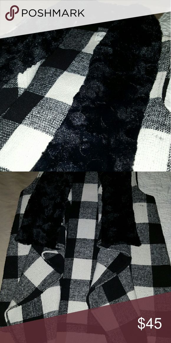 Vest Black and white checkerd vest with a black fur collar. Its lightweight enough to be flowy but still warm. Brand new from decadence boutique, just to big for me. Very cute with skinny jeans and boots Jackets & Coats Vests