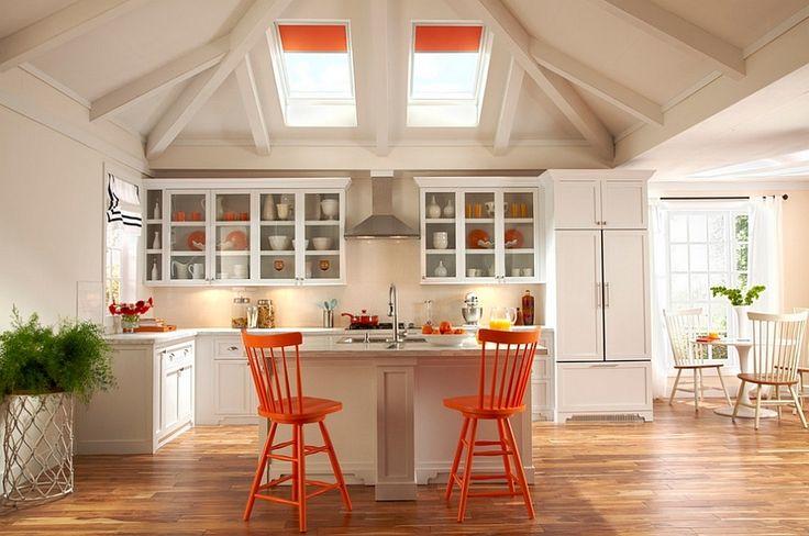 Совпадение цвета рулонных штор на мансардных окнах, барных стульев и некоторой посуды объединяет интерьер этой кухни. .