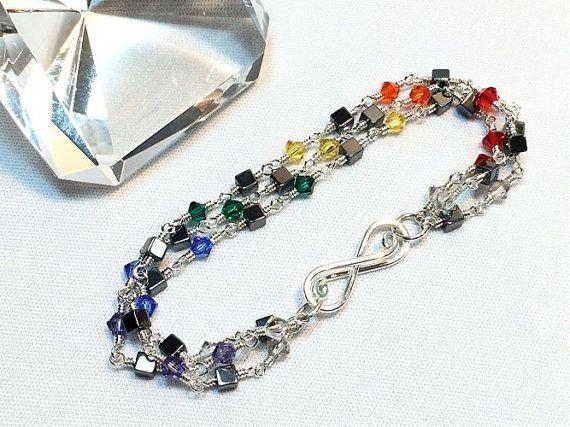 Esta pulsera de cadena de plata tres con cristales de Swarovski de color de arco iris es ingeniosamente envuelto en alambre de plata esterlina con construcción de bucle cerrado para una creación eterna. He utilizado hematita cubo y 24 cristales de Swarovski en rojo, naranja, amarillo, verde, azul, púrpura y gris satén de color de arco iris. Longitud total es de 7 1/2 pulgadas de largo y 1/2 pulgada de ancho. Para completarlo añadí mi firma cierre infinito en un alambre de grueso calibre para…