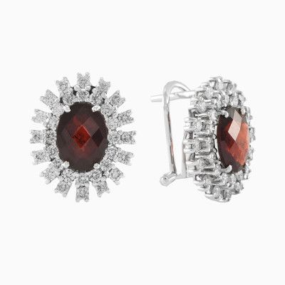 Classic pair of diamond earrings with garnet in 18k white gold. Each earring features an oval shaped dark red garnet with total weight 2.33 ct. Garnet framed in a dazzling border of round brilliant cut diamonds with a total weight 0.90 ct.