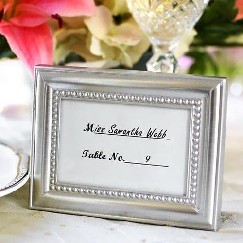"""This graceful beaded picture frame can be used as place card holders, party favors or the brushed metal frame can hold a 2"""" x 3"""" photograph. Each comes with a pre-printed place card that can be filled in with the name and table number for each guest."""