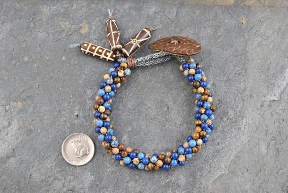 Lapis Lazuli/Picture Jasper/Tiger Eye Kumihimo Artisan Bracelet #bracelet #kumihimo #kumihimobracelet #artisan #artisanbracelet #oneofakind #handmade #handwoven #woven #handknotted #gemstone #natural #naturalgemstones #lapis #lapislazuli #jasper #picturejasper #tigereye #tribal #tribalstyle #boho #bohemian #handcarved #bone #bonebeads #handcarvedbonebeads #coconut #coconutfibrebutton #unique #earthy #lightweight #flexible