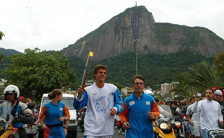 O tenista brasileiro Gustavo Kuerten conduz a tocha olímpica sob a estátua do Cristo Redentor, durante revezamento no evento de condução do fogo simbólico da Olimpíada, no Rio de Janeiro, em 2004.  Fotografia: Antônio Gaudério/Folhapress.