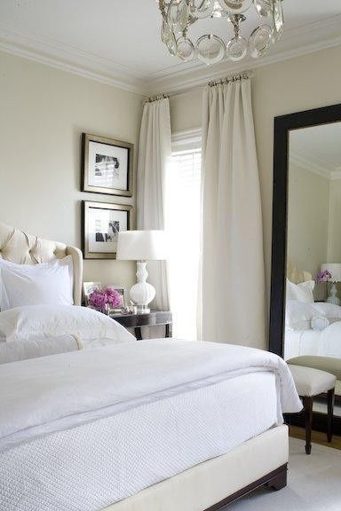 Light beige walls with same tone curtains & white bedding with dark furniture