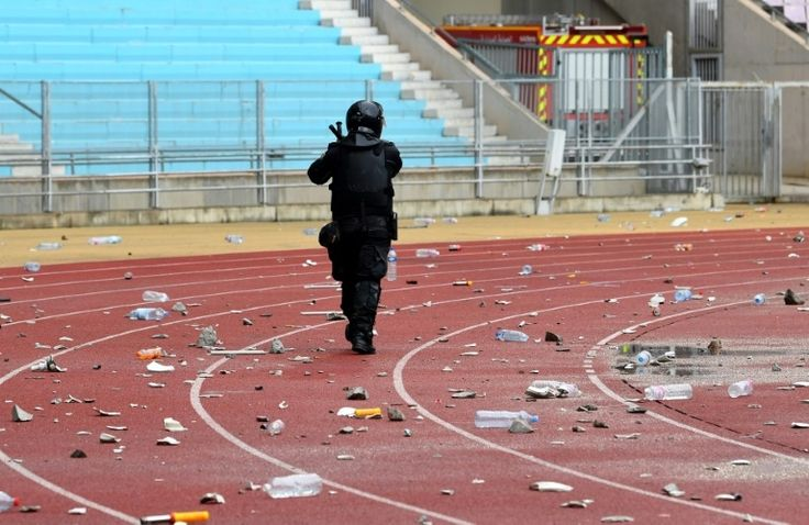 A policeman walks past debris on the ground following the Tunisia Ligue 1 football match derby between Esperance Sportive de Tunis and Club Africain at the Stade Olympique of Rades in Tunis.AFP – FETHI BELAID
