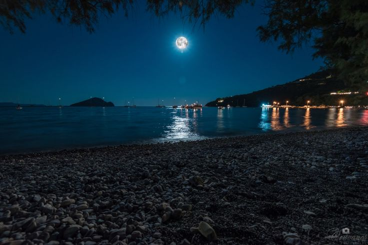 Celebration of the full moon in Zakynthos. They are singing greek Zakynthian (traditional) songs inside the boats under the moonlight.