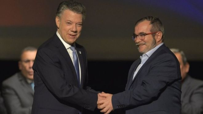 Colombian President Juan Manuel Santos (L) and the head of the FARC guerrilla Timoleon Jimenez, aka Timochenko, shake hands during the second signing of the historic peace agreement between the Colombian government and the Revolutionary Armed Forces of Colombia (FARC), at the Colon Theater in Bogota, Colombia, on November 24, 2016.