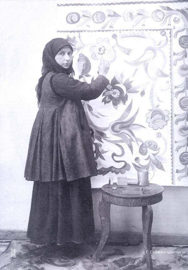 Ганна Собачко на фоні своєї роботи, с.Скопці, кустарна майстерня Семиградової, 1915