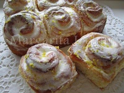 Лимонные булочки с глазурью Тесто:  200 мл молока (тёплое)  1 п. сухих дрожжей (7 г)  50 г сахара  2 яйца   0,5 ч. л. соли   ванил.  цедра от 2 лимонов  100 г слив масла  550 г муки (просеять)  Начинка:  200 г сахара  цедра 1 лимона  40-50 мл сока лимона Сливочная глазурь:  120 г сливочного сыра  30 мл сока лимона  100 г сахарной пудры Готовые горячие булочки полить с помощью ложки глазурью и потереть сверху цедру от одного лимона.