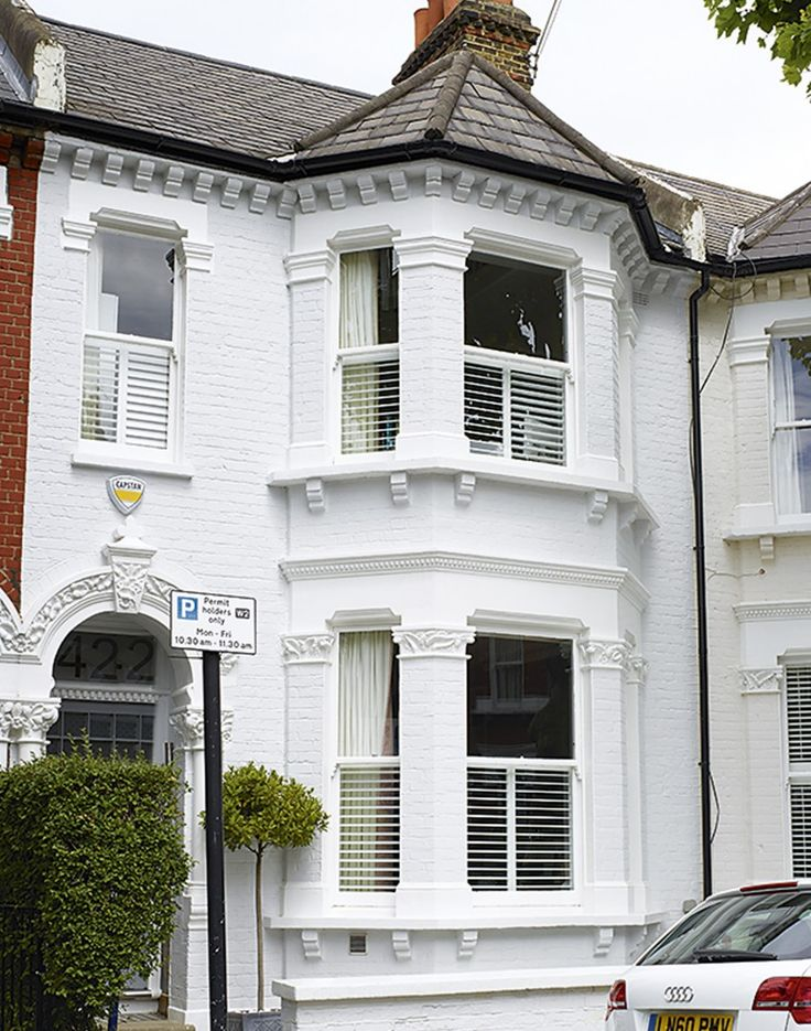 victorian terraced house with white painted exterior middle line in the window achieved through the