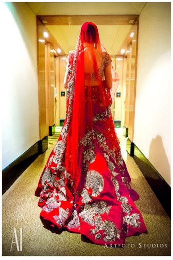 Bridal Lehengas - Red Bridal Lehenga with Trail Behind | WedMeGood | Red Lehega with Silver Embroidery and a Net Dupatta #wedmegood #indianbride #indianwedding #trail #lehenga #bridal #silver