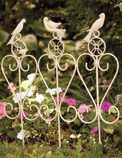 Decorative wrought iron garden edging featuring a gathering of songbirds, creating the perfect border for flower beds.