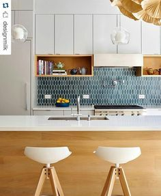 Modern kitchen with white cupboards, chairs and counter with teal tiled backsplash