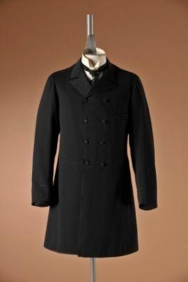 Zwarte wollen redingote met een dubbele rij knopen en een horizontale naad in de taille. De rokpanden waren recht en eindigden in het midden van het dijbeen. De mantel werd gecombineerd met een rechte lange broek, een korte gilet en een hemd met een hoge stijve kraag. De redingote werd aan het einde van de 19e eeuw frock coat genoemd | Modemuseum Hasselt | ca. 1890-1900
