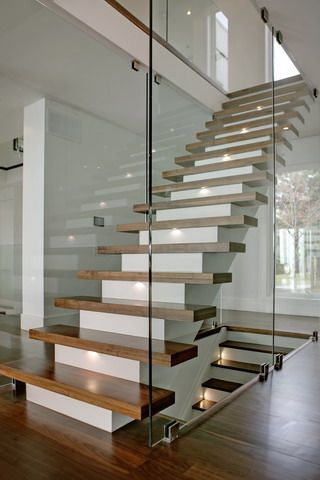 Floating wooden stairs on a white base staircase with frameless partition